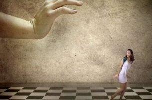 Meisje dat bang is om verpletterd te worden door een grote hand als voorbeeld van gaslighting