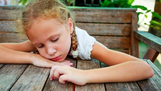 Meisje dat doelloos en ongelukkig over een tafel hangt als voorbeeld van depressie bij kinderen