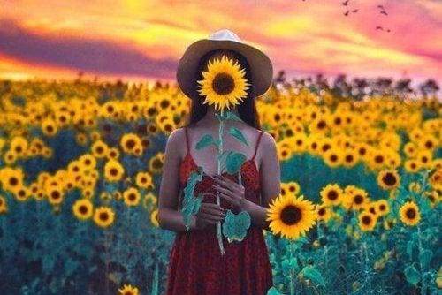Meisje dat in een veld met zonnebloemen staat en een zonnebloem voor haar gezicht houdt op zoek naar een antwoord op de vraag wat maakt gelukkig