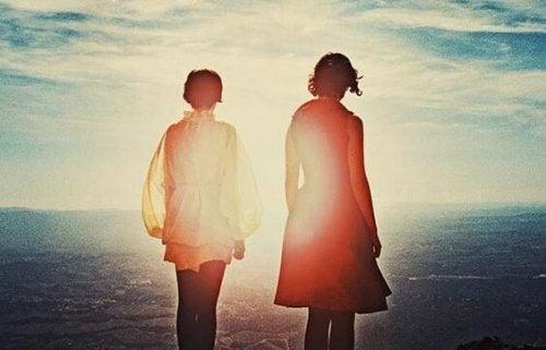Twee meisjes die over de zee uitkijken