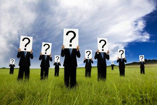 Mannen die allemaal een bord met een vraagteken er op voor hun gezicht houden als voorbeeld van prosopagnosie
