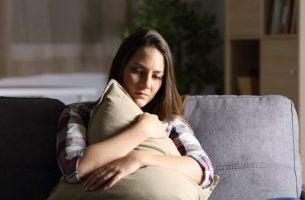Vrouw die op de bank zit en een kussen vasthoudt vanwege de zondagsblues, de melancholie op zondagen