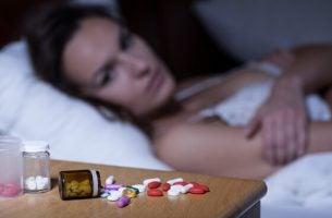 Vrouw kijkt naar haar slaappillen, als voorbeeld voor het verslavende effect van benzodiazepinen
