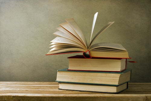 Stapel boeken waarvan het bovenste boek opgeslagen ligt