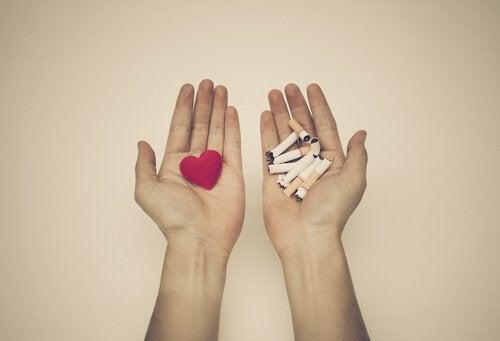 Twee handen waarvan er in een een hartje ligt en in de andere gebroken sigaretten als hulp bij stoppen met roken