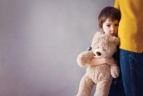 Verlegen kind met teddybeer dat schuilt achter zijn ouder