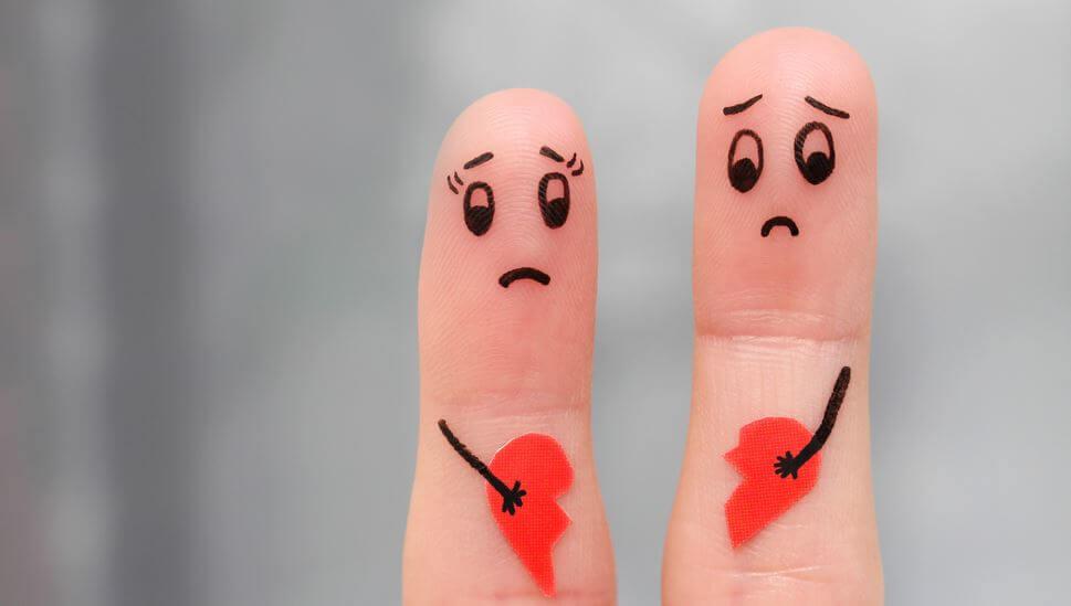 Twee verdrietige vingers die ieder een deel van een gebroken hart vasthouden vanwege een breuk in hun relatie