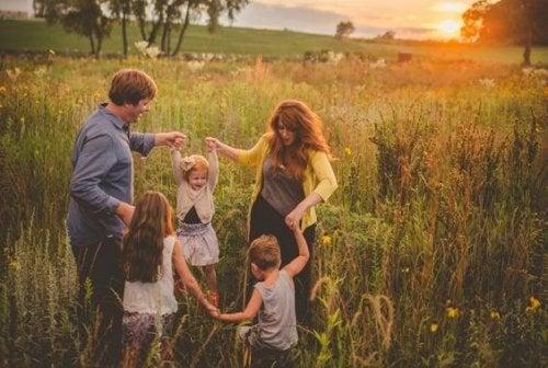 Een gezin dat vrolijk speelt in een weiland bij zonsondergang
