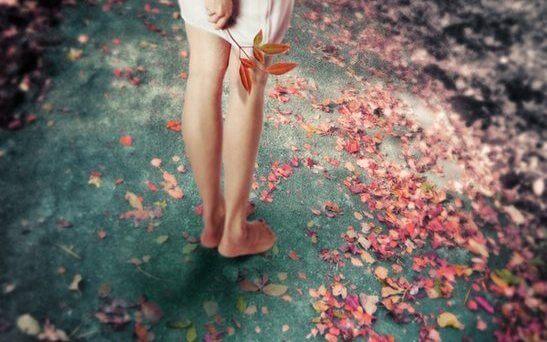 Vrouw die op haar blote voeten door de blaadjes loopt want leven in het nu is belangrijk voor haar