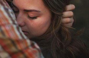 Vrouw huilt bij partner en durft zich kwetsbaar op te stellen.