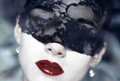 Vrouw met een kanten doekje om haar ogen gebonden en rode lippenstift op haar lippen
