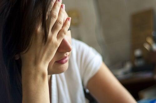 Vrouw houdt haar hand bij haar hoofd omdat ze last heeft van hoofdpijn