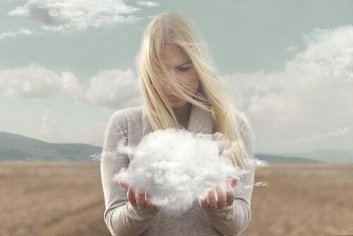 Vrouw die een donderwolk vasthoudt die de oorzaak is van al haar problemen als voorbeeld van zelfbedrog