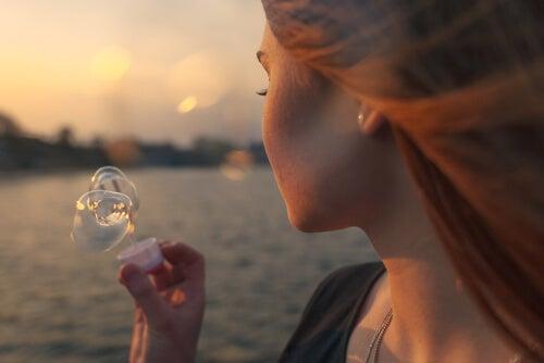 Meisje dat bellen blaast met de wind om een pijnlijke gebeurtenis te vergeten of moet ze ermee leren leven