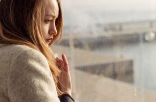 Meisje dat droevig voor zich uit kijkt omdat ze een pijnlijke gebeurtenis wil vergeten of moet ze ermee leren leven