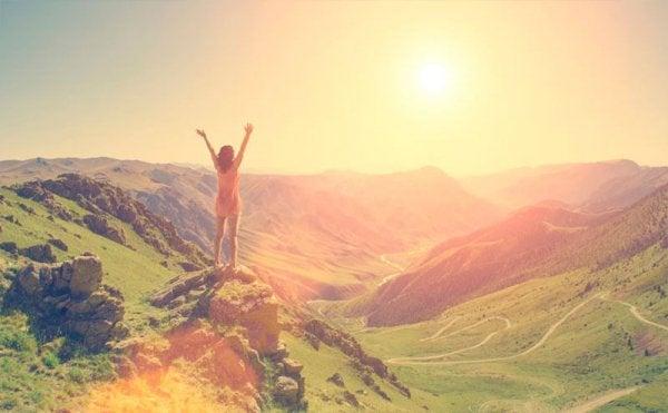 Vrouw die van blijdschap haar armen in de lucht steekt want ze heeft de top van de berg bereikt en kan taai zijn