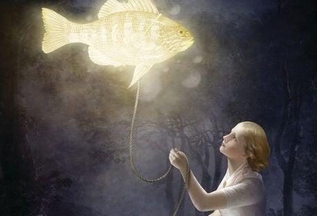 Vrouw die een vis vasthoudt aan een touw en die vis geeft licht