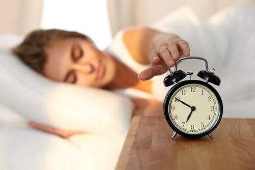 Vrouw die na een nacht heerlijk slapen haar wekken uitzet