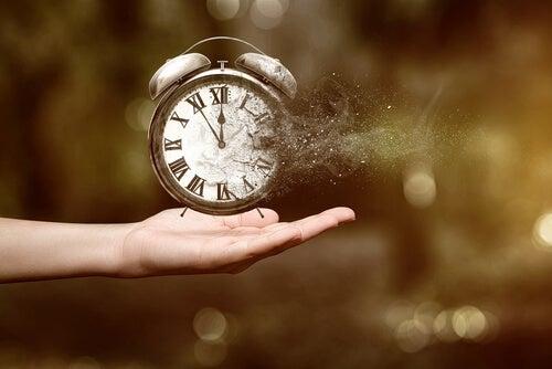 Meisje die een klok vasthoudt die langzaam in stof verandert want de 1-minuutregel helpt om luiheid tegen te gaan