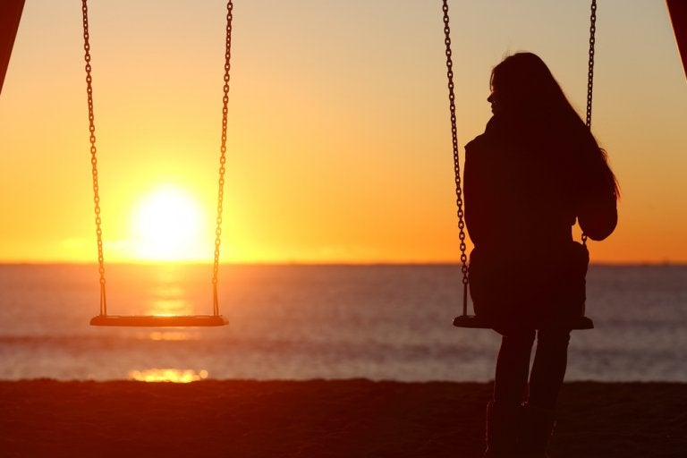 Vrouw op schommel bij ondergaande zon