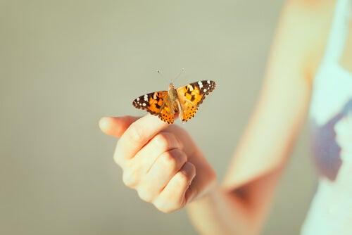 Meisje dat een vlinder op haar vinger houdt