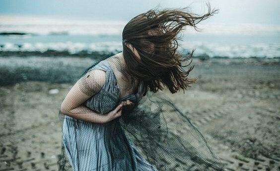 Vrouw die van de pijn voorover buigt alsof ze geraakt is door een kogel als voorbeeld van zelfdestructieve mensen