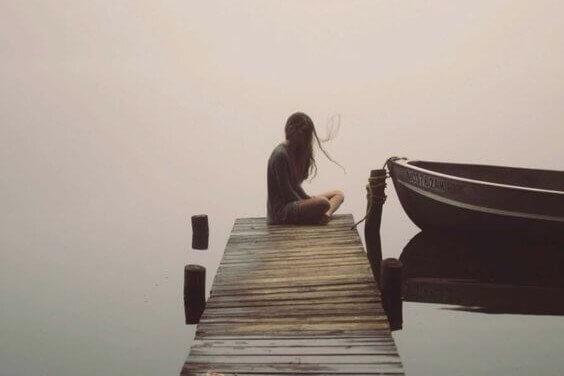 Meisje dat in haar eentje op een verlaten steiger zit