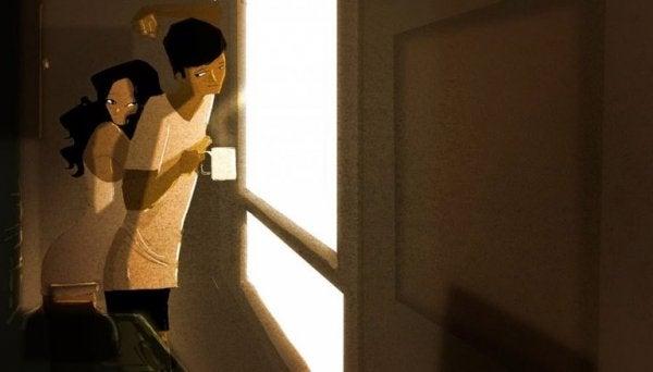 Vriend en vriendin die knuffelend uit het raam kijken