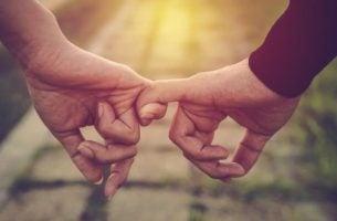 Twee mensen die elkaar pinkie's vasthouden, maar niet vanuit aanhankelijkheid