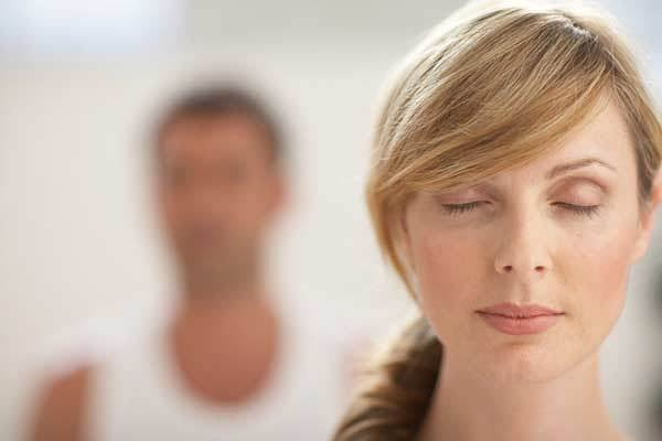 Vrouw die haar ogen sluit om tot rust te komen en haar mentale controle te vergroten