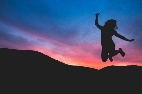 Vrouw die bij zonsondergang een sprong in de lucht maakt vanwege haar persoonlijk empowerment