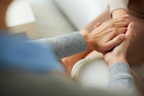 Psycholoog die de hand van zijn patient vasthoudt