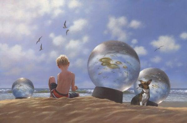 Jongetje zit op het strand te spelen tussen de glazen bollen