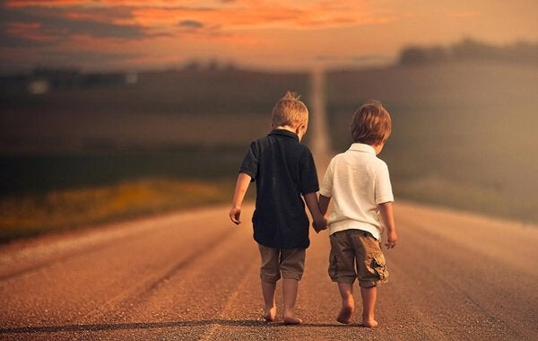 Twee jongetjes die samen op blote voeten over een grote weg lopen