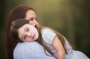 Kind laat haar hoofd rusten op de schouders van haar moeder, bij wie ze zich veilig voelt omdat haar moeder weet dat schreeuwen tegen je kind niets oplost