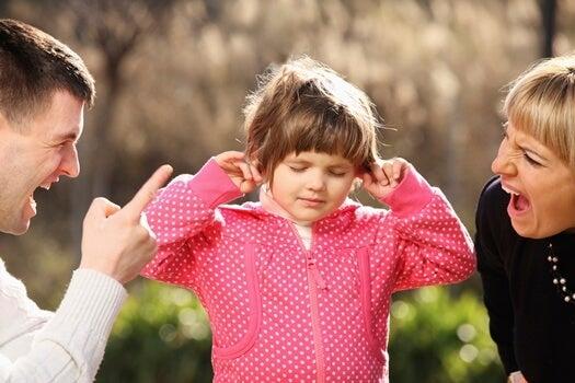 Klein meisje houdt haar oren dicht voor het geschreeuw van haar ouders, die niet weten dat schreeuwen tegen je kind niets oplost