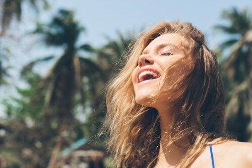 Lachende vrouw die destructieve kritiek naast zich neer kan leggen