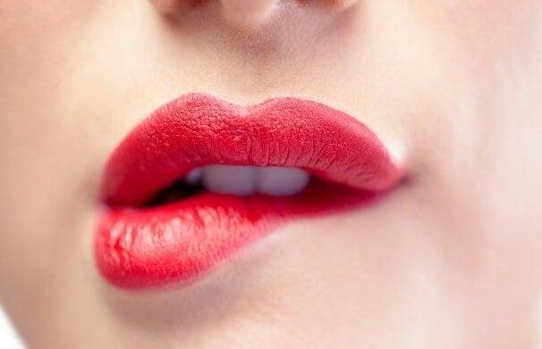 Vrouw met rode lippenstift op die op haar lip bijt en dit kan wantrouwen oproepen