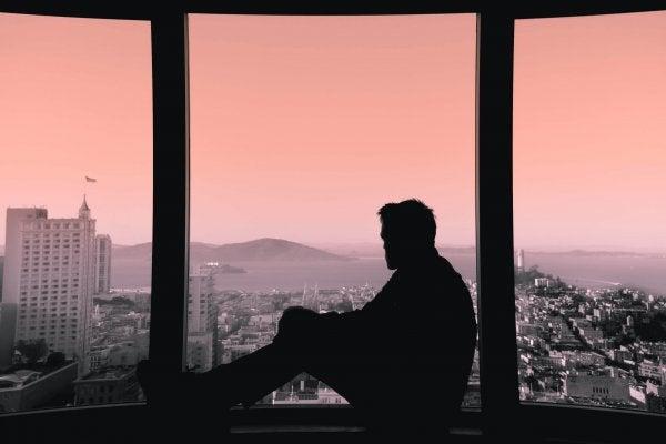 Man die verlangend uit het raam kijkt en weet dat iemand missen niet hetzelfde is als iemand terugwillen