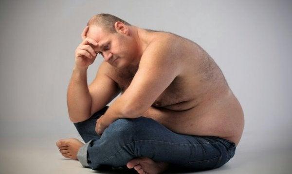 Een vrij dikke mannen die nadenkt over de relatie tussen emoties en obesitas