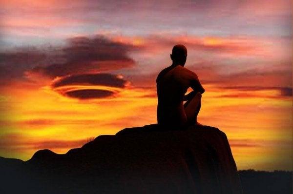 Man die van een rots zit te kijken naar de zonsopgang