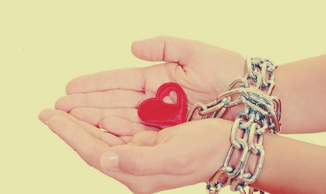 Meisje wiens handen zijn vastgebonden met een ketting die een hartje als slot heeft