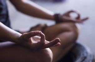 Vrouw die in de lotushouding zit want beginnen met mediteren begint bij de juiste houding