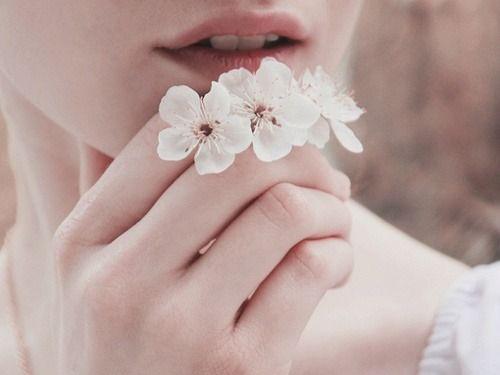 Meisje dat een paar witte bloemetjes vasthoudt als voorbeeld van hoe mooi het minimalisme kan zijn en waarom minimalist worden mooi kan zijn