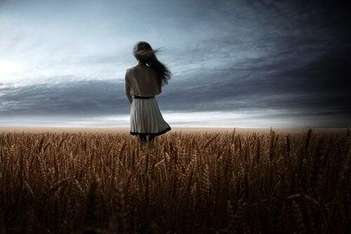 Meisje dat in een granenveld naar de donkere wolken staat te kijken