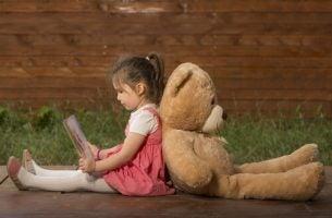 Meisje dat tegen haar teddybeer aanleunt om een boek te lezen