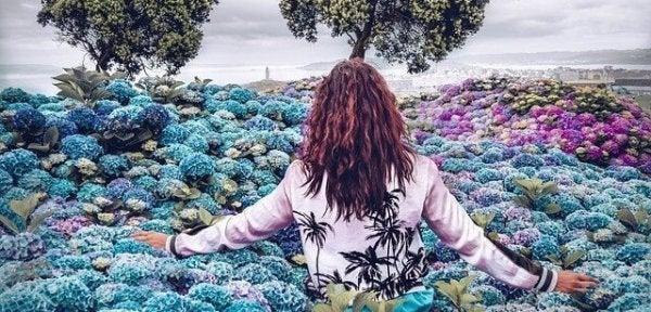 Vrouw tussen de blauwe en paarse bloemen