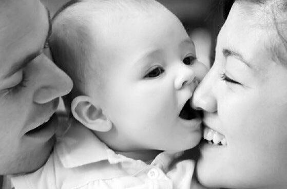 Twee ouders die hun gezicht tegen het gezicht van hun pasgeboren baby aan drukken en duidelijk geen vermijdende hechtingsstijl hebben