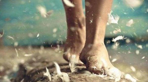 Vrouw die op blote voeten over veren loopt en geniet van mindfulness in het dagelijks leven