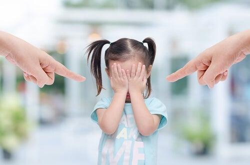 Meisje dat met haar handen voor haar ogen staat omdat er twee grote vingers naar haar wijzen
